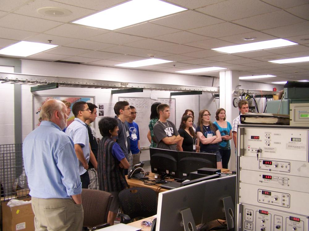 A group of students and chaperones looking toward an off-frame subject, obscured behind machinery, in a classroom computer lab